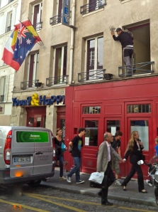 This guy leaning out of a second-floor window is installing flag holders for Young and Happy, a youth hostel.