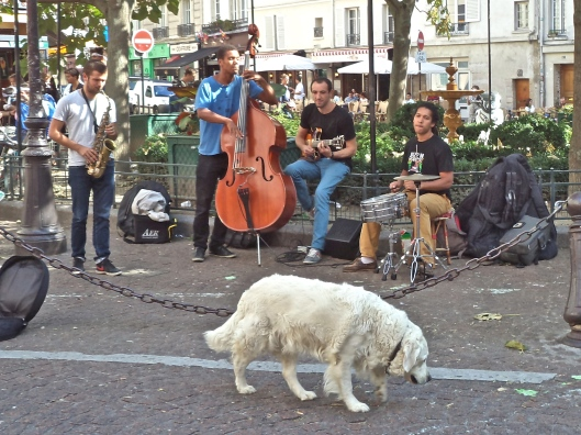 There is plenty of room for performers and pets on the Place Contrescarpe.  Usually the square is crowded, but this week the tourists are gone.  So there are plenty of chairs in the cafés, and you can hear the music and the splashing of the fountain.