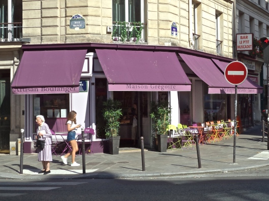 The bakery around the corner from my apartment has hung a new purple awning and put out multicolored tables and chairs.  Today a lovely lady in a purple suit adds a decorative touch.